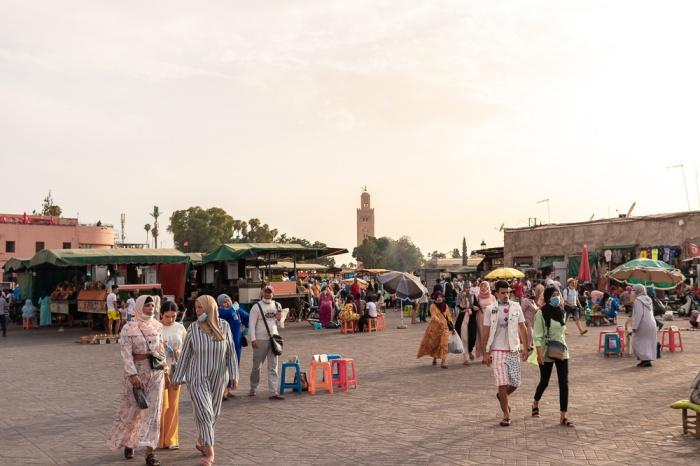 Pessoas na praça principal de Marraquexe com mesquita ao fundo