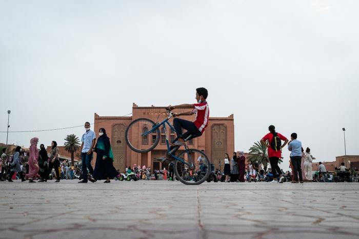 Jovem a andar de bicicleta na Praça Al-Mouahidine em Ouarzazate