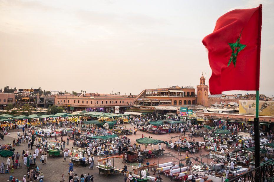 Vista sobre a praça principal de Marraquexe com bandeira de Marrocos